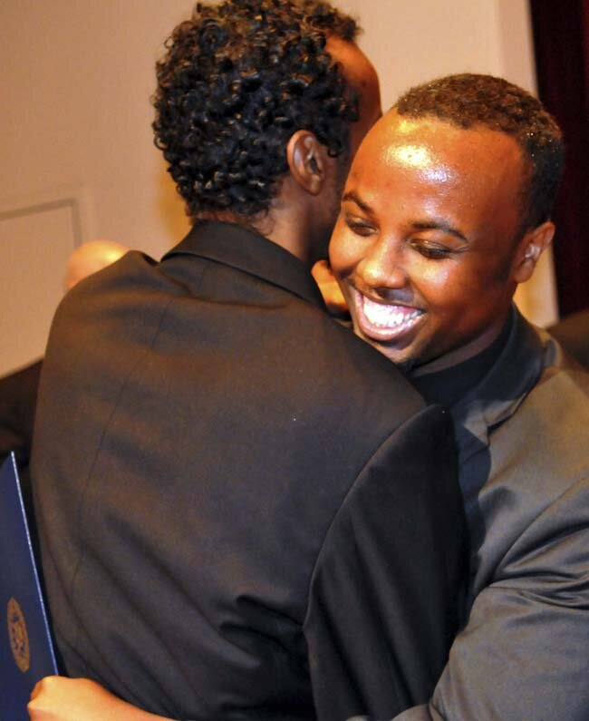 Ka Joog executive director Mohamed Farah, right, is embraced by Abdimalik Mohamed, Ka Joog director of operations, after the organization they founded received the FBI Director's Community Leadership Award on Wednesday at Augsburg College in Minneapolis. (Pioneer Press: John Doman)