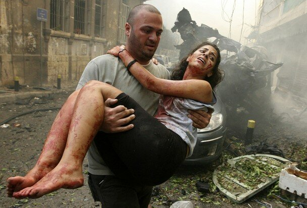 A wounded woman is carried at the site of an explosion in Ashrafieh