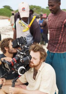 """Director Cutter Hodierne, bottom right, on the set of """"Fishing Without Nets."""" To Cutter's left is director of photography Alex Disenhof. The two Kenyan men behind Cutter and Disenhof are from the local village in Mambrui."""